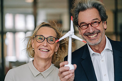 Portrait of happy businessman and businesswoman holding wind turbine model in office - p300m2156201 by Gustafsson