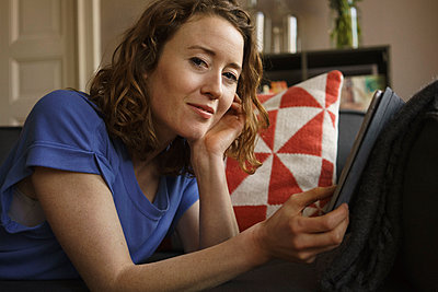 Portrait of confident woman using digital tablet on sofa at home - p301m1579775 by Halfdark