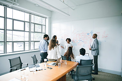 Businesswoman talking near whiteboard in meeting - p555m1504091 by John Fedele