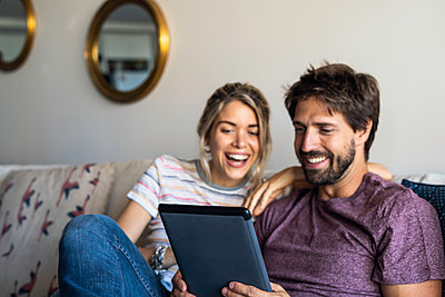 Couple using digital tablet at home - p623m2165368 by Frederic Cirou