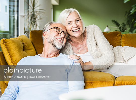 Smiling mature woman leaning on man while resting on sofa - p300m2294156 by Uwe Umstätter