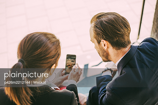 Rear view of business people looking in phone while sitting outdoors - p426m2212144 by Maskot