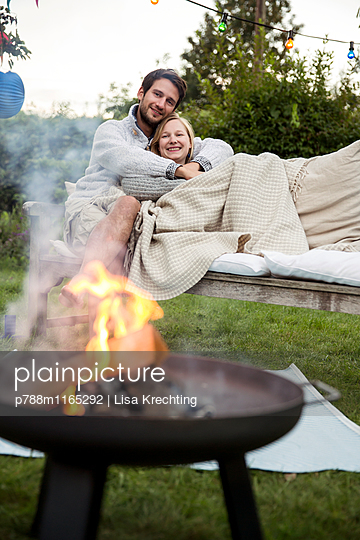 Young couple cuddling on garden bench - p788m1165292 by Lisa Krechting