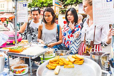 Thailand, Bangkok, Khao San Road, group of friends choosing local food on street market - p300m1581336 by William Perugini