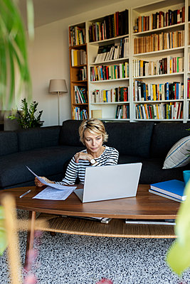 Mature woman with documents using laptop at home - p300m2144794 by Valentina Barreto