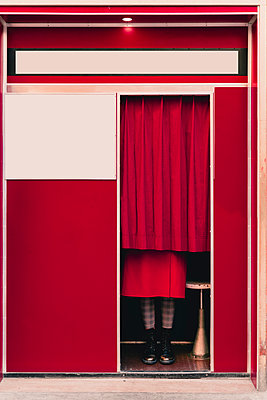 Woman wearing red coat and boots standing behind curtain in a photo booth - p300m2170159 by Francesco Morandini