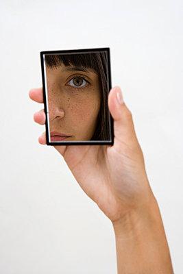 A woman looking into a hand mirror - p3016805f by Halfdark