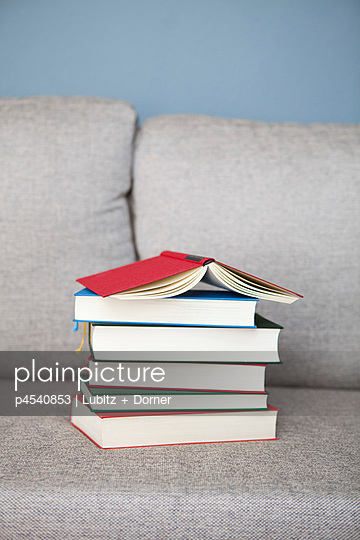 Stack of books on a sofa - p4540853 by Lubitz + Dorner