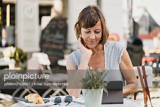 Mature woman using laptop in sidewalk cafe - p586m2109097 by Kniel Synnatzschke
