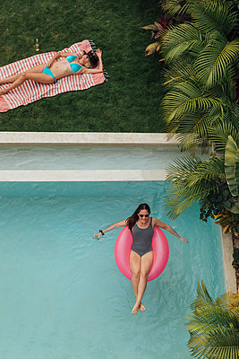 Two young women relaxing at swimming pool - p300m2103470 by letizia haessig photography