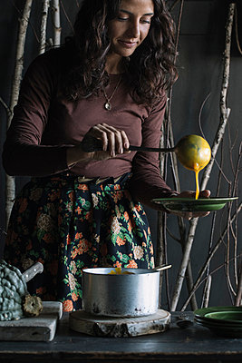 Young woman ladling fresh soup from saucepan at rustic kitchen counter - p429m2052169 by Alberto Bogo