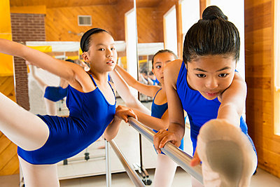 Ballerinas warming up at the barre in ballet school - p924m825938f by Florin Prunoiu