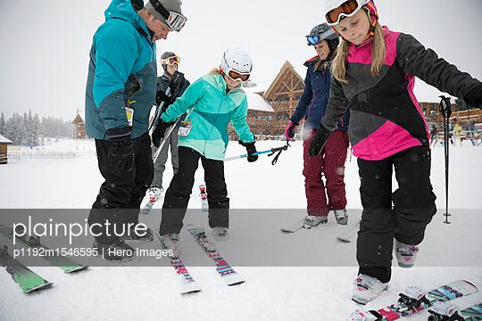plainpicture | Photo library for authentic images - plainpicture p1192m1546595 - Family skiers preparing ski... - plainpicture/Hero Images