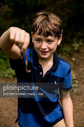 Junge mit Regenwurm im Wald - p1212m1152940 von harry + lidy