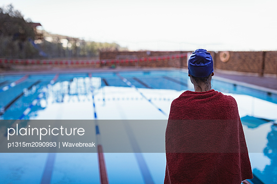 Young female swimmer wrapped in towel standing near swimming pool - p1315m2090993 by Wavebreak
