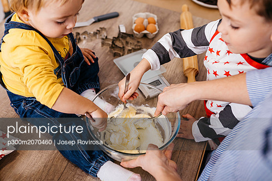 Mother and children preparing dough together - p300m2070460 by Josep Rovirosa