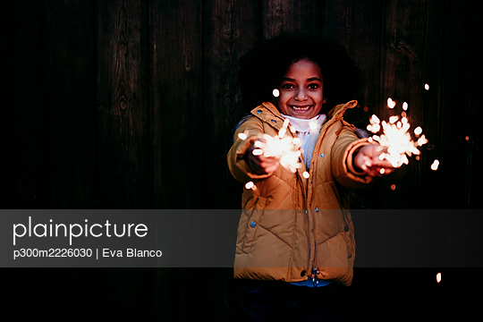 Smiling girl standing and playing with sparkler at night - p300m2226030 by Eva Blanco