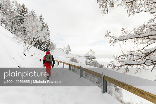 Man hiking in snowy mountain path - p300m2256955 by Michela Ravasio