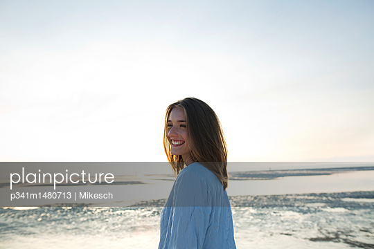 Happy young woman right beside the sea - p341m1480713 by Mikesch
