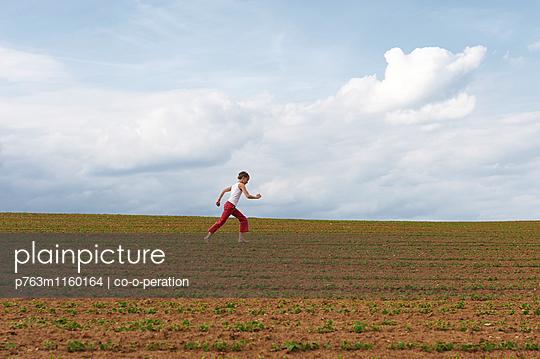 Laufendes Mädchen auf dem Feld - p763m1160164 von co-o-peration