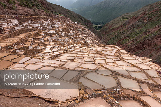 Mountain landscape with Moray Maras terraced salt mine in the foreground near Cusco, Peru.  - p924m2196779 by Guido Cavallini