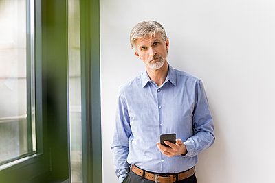 Mature man using smartphone - p300m1587777 by Jo Kirchherr