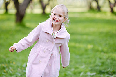 Portrait of happy little girl wearing pink coat - p300m2167052 von Ekaterina Yakunina