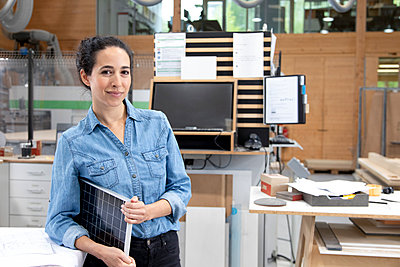 Businesswoman with solar panel model in factory - p300m2265205 by Florian Küttler