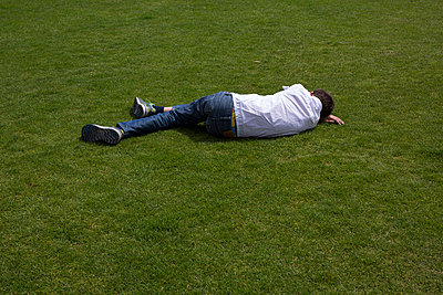 Child lying in the grass - p445m1040050 by Marie Docher