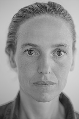 Portrait of woman with a serious face - p552m2204128 by Leander Hopf