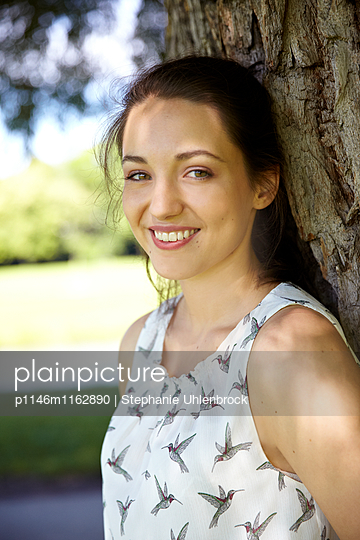 Junge Frau lehnt an einem Baum - p1146m1162890 von Stephanie Uhlenbrock