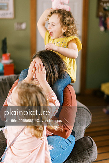 A young mother playing wild with her children in the living room - p1166m2269698 by Cavan Images