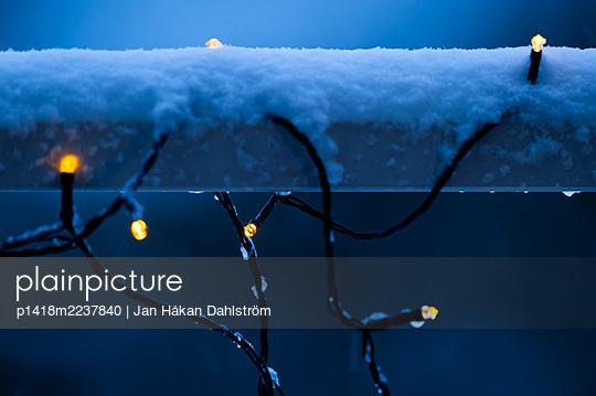 Electric lights on snowy fence - p1418m2237840 by Jan Håkan Dahlström
