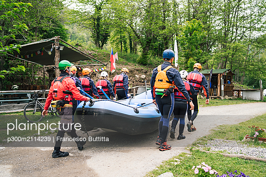 Group of friends preparing for a rafting trip carrying rubber dinghy - p300m2114239 von Francesco Buttitta