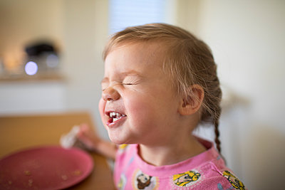 Cute toddler girl making funny faces at the table. - p1166m2163002 by Cavan Images
