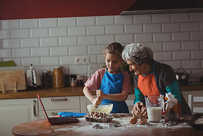 Grandmother and granddaughter preparing cookies in kitchen at home - p1315m1566659 by Wavebreak
