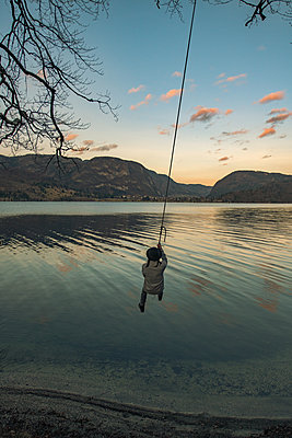 Young man on a swing next to Bohinj Lake in Slovenia - p1455m2077117 by Ingmar Wein