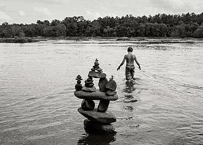 Boy Walking with Balanced Rocks - p1503m2015867 by Deb Schwedhelm
