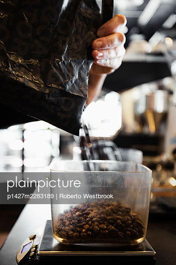 Coffee shop barista pouring coffee beans, close-up - p1427m2283189 by Roberto Westbrook