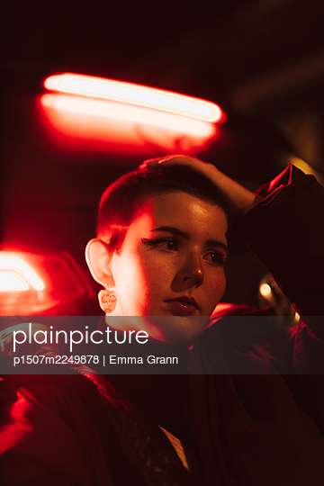 Young woman in red light, portrait - p1507m2249878 by Emma Grann
