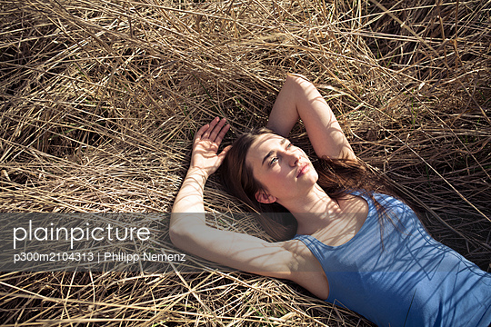 Relaxed young woman lying in meadow - p300m2104313 von Philipp Nemenz