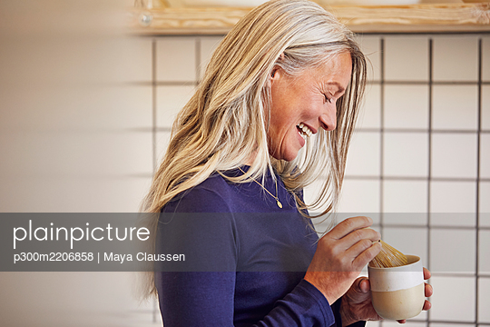 Smiling woman mixing tea in kitchen - p300m2206858 by Maya Claussen