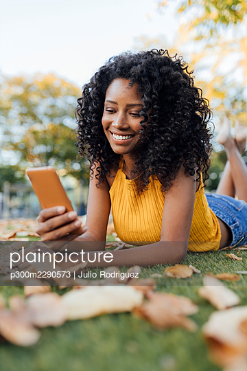 Smiling young woman text messaging through smart phone lying on grass at park - p300m2290573 by Julio Rodriguez