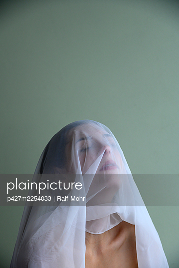 Woman with veil over her face, portrait - p427m2254033 by Ralf Mohr