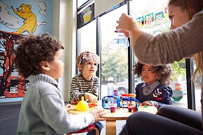 Teacher showing science experiment to children at preschool - p1166m1097517f by Cavan Images