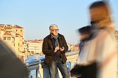 Man standing with smartphone on a bridge - p1312m2082153 by Axel Killian