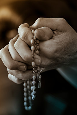 Female hands folded for prayer, holding a rosary. - p1433m1589013 by Wolf Kettler