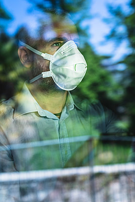 Mature pensive man with protective mask looking out of the window - p300m2180475 by 27exp