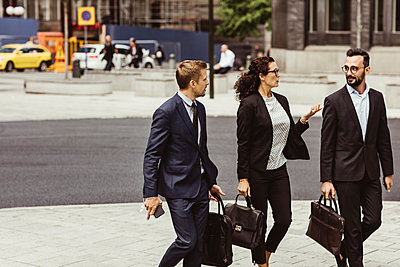 Female entrepreneur discussing business strategy with male coworkers while walking outdoors - p426m2169599 by Maskot