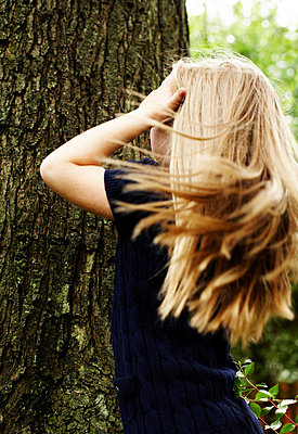 Young Blond Girl Standing Against Tree Trunk, Rear View - p694m663760 by Maria K